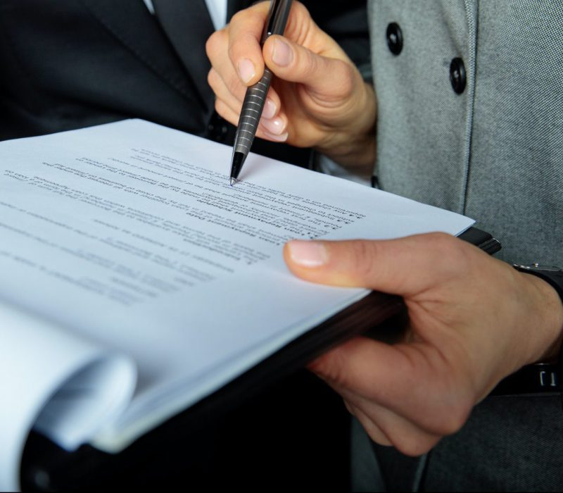 Close-up partial view of businesspeople discussing and signing papers